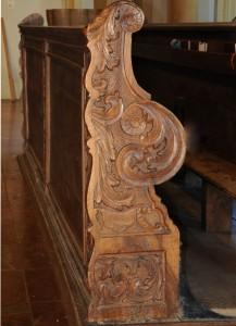 Reliefschnitzereien auf den Wangen der Kirchenstühle